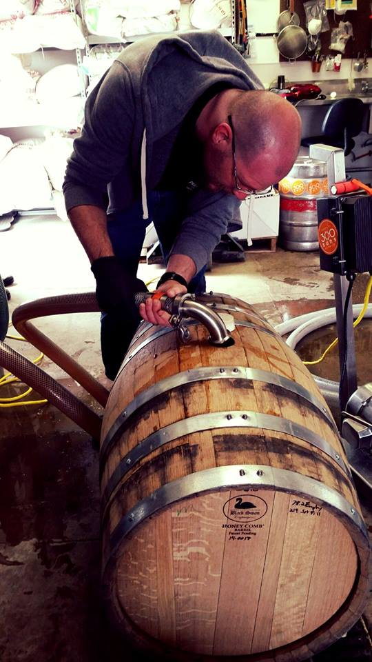 Dan putting Old Burlington Stout into whiskey barrels.